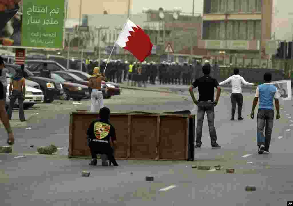Manifestantes en contra del régimen de Bahréin se enfrentan con la policía, que intenta prevenir con gases lacrimógenos que los manifestantes pro-democracia se unan a una demostración que se realiza a las afueras de Mana