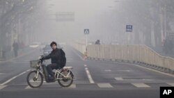 FILE - A man rides an electric bike crossing a street shrouded by haze in Beijing.