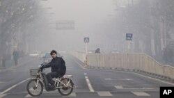 Seorang warga melintasi jalanan Beijing yang penuh asap polusi (foto: dok). Pemerintah China menerapkan target ambisius untuk menciptakan udara bersih di wilayah perkotaan.