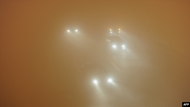 Picture taken on January 14, 2013 shows vehicles running slowly in heavy fog in Hefei, central China's Anhui province.