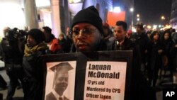 FILE - A protester holds a sign as people rally in memory of 17-year-old Laquan McDonald, who was shot 16 times by police officer Jason Van Dyke in Chicago, Nov. 24, 2015.
