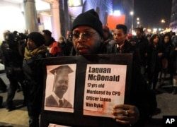FILE - A protester holds a sign as people rally in memory of 17-year-old Laquan McDonald, who was shot 16 times by Chicago Police Department Officer Jason Van Dyke, in Chicago, Nov. 24, 2015.