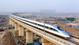 FILE - A high-speed train travelling to Guangzhou is seen running on Yongdinghe Bridge in Beijing, December 26, 2012.