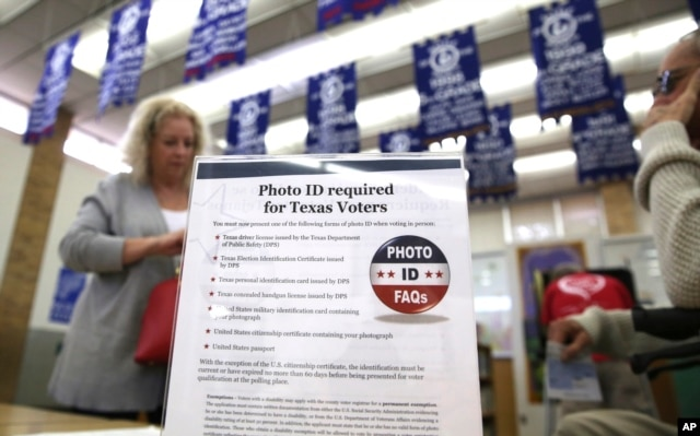 A sign tells voters of voter ID requirements before participating in the primary election at Sherrod Elementary school in Arlington, Texas, March 1, 2016.