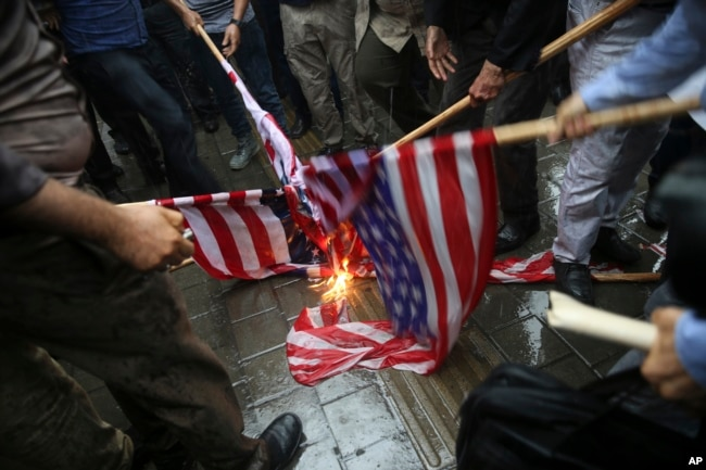 FILE - Iranian demonstrators burn representations of the U.S. flag during a protest in front of the former U.S. Embassy in response to President Donald Trump's decision to pull out of the nuclear deal and renew sanctions, in Tehran, Iran, May 9, 2018.