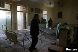 People inspect damage in Omar Bin Abdulaziz hospital, in the rebel-held besieged area of Aleppo, Syria, Nov. 19, 2016.