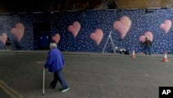 Australian street artist James Cochran, also known as Jimmy C, works, March 26, 2018, on his mural with eight hearts, each representing one of the eight victims of the attack that took place on London Bridge and around Borough Market in 2017.