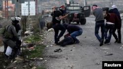 اسرائیلی سیکیورٹی اہل کار ایک فلسطینی کو گرفتار کر رہا ہے۔ 14 دسمبر 2017