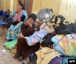 FILE - Egyptian Coptic Christians sit in the courtyard of the Evangelical Church in the Suez Canal city of Ismailiya, Feb. 24, 2017, upon arriving to take refuge from Islamic State group jihadists.