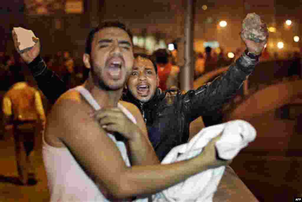 January 26: A protester, right, holds rocks in the air, ready to throw at riot police, as he urges other protesters on, during clashes in Cairo, Egypt, in the early morning. Egyptian police fired tear gas and rubber bullets and beat protesters to clear th