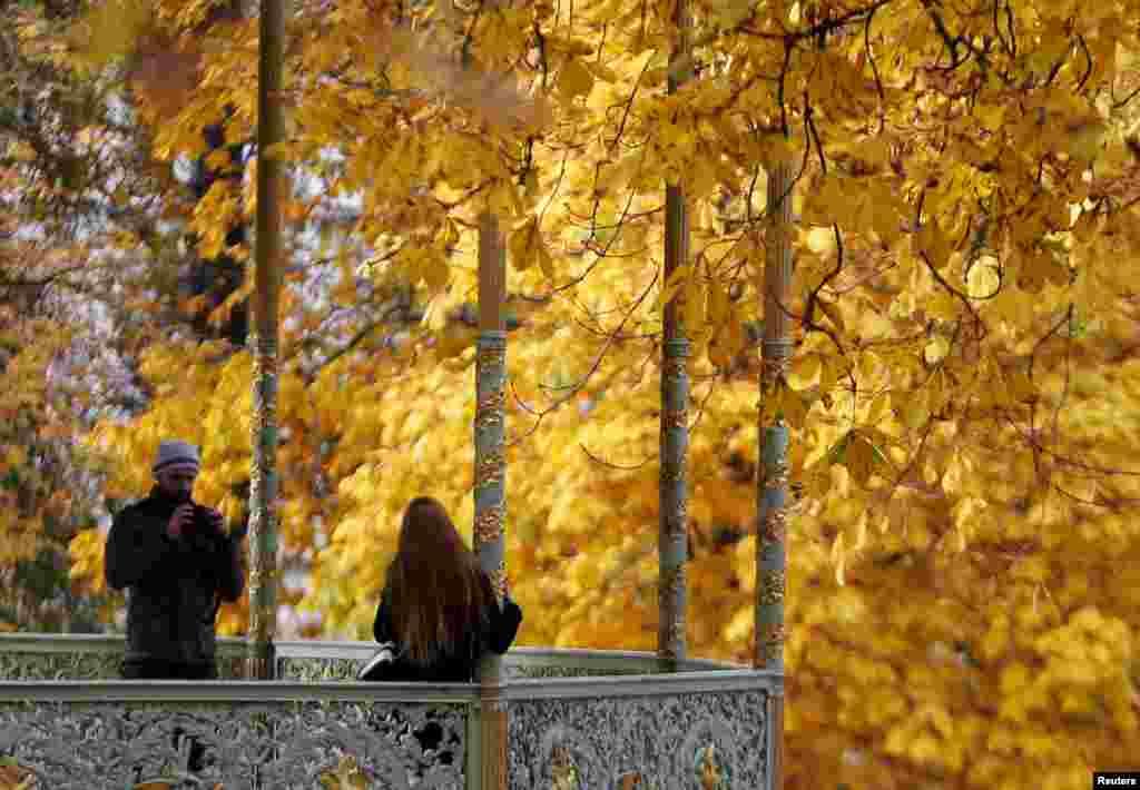 Một người phụ nữ chụp hình trong một ngày mùa thu nhiều nắng trong công viên Brussels gần Cung điện Hoàng gia, Bỉ.