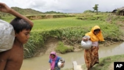 Rohingyas carry water from a pond near a refugee camp in Cox's Bazar Bangladesh, August 19, 2011.