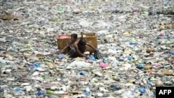 지난해 3월 필리핀 마닐라 시의 오염된 강에서 한 남성과 어린이가 플라스틱 병을 수거하고 있다. (자료사진)
