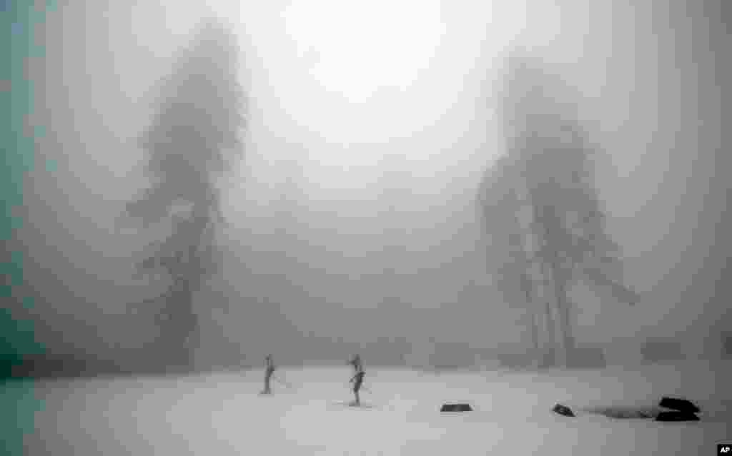 Athletes train as fog enshrouds the course of the men's biathlon 15k mass-start, at the 2014 Winter Olympics, Feb. 17, 2014.