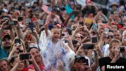 """Yon bebe ki t ap fè drapo ameriken an flote devan Prezidan Donald Trump ak Premyè Dam nan, Melania Trump, pandan yo t ap rive devan Moniman Lincoln nan pou sa Misye Trump rele """"Omaj pou Lèzetazini"""" nan Washington D.C., 4 jiyè 2019 la."""