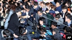 Choi Soon-sil, center left wearing black hat, a cult leader's daughter with a decades-long connection to President Park Geun-hye, is surrounded by prosecutor's officers and media at the Seoul Central District Prosecutors' Office in Seoul, South Korea, Oct. 31, 2016.