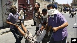 Anti-government protesters carry an injured fellow protester during clashes in the southern Yemeni city of Taiz, April 5, 2011