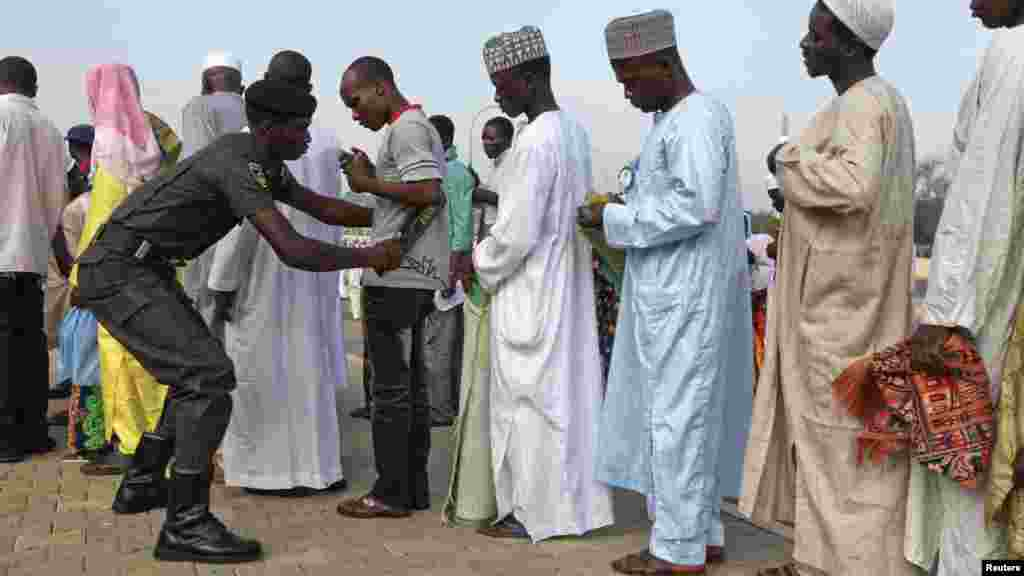 A policeman scans people before the start of prayers in Abuja.