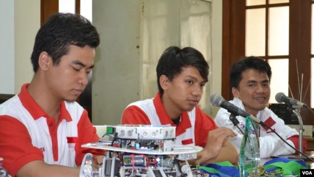 Tiga Anggota Tim Robot UGM, (dari kiri: Bakhtiar C Permana, Agys Badruzzaman dan Malik Kheer) berpose bersama robot hasil karya mereka (VOA/Nurhadi)