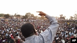 Ugandan opposition leader Kizza Besigye makes a speech during a protest rally against the rising cost of living and commodities in the Namungoona suburb of Kampala, January 24, 2012.