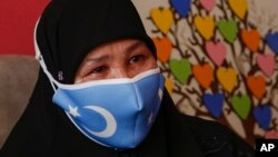 Bumeryem Rozi, 55, an ethnic Uyghur who fled from China to Turkey, cries as she talks to The Associated Press, at her home, in Istanbul, Tuesday, June 1, 2021. (AP Photo/Mehmet Guzel)
