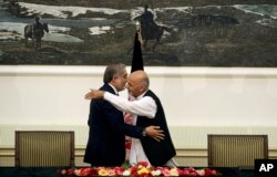 Afghanistan's presidential election candidates Abdullah Abdullah, left, and Ashraf Ghani Ahmadzai, right, hug after signing a power-sharing deal at presidential palace in Kabul, Afghanistan, Sept. 21, 2014.
