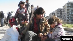 FILE - Syrian children sit with their belongings as they wait to be evacuated from a besieged area of Homs Feb. 12, 2014.