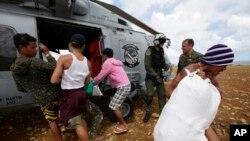 Cư dân bị mắc kẹt dỡ hàng cứu trợ từ một máy bay trực thăng của Hải quân Hoa Kỳ cho những người bị cô lập bởi siêu bão Haiyan, 16/11/2013