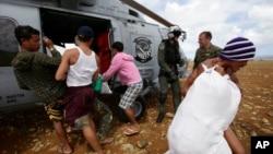 Warga membantu menurunkan bantuan darurat untuk para korban topan Haiyan yang terisolasi di pulau Manicani, sebelah Timur provinsi Samar, Filipina Tengah dari helikopter Tentara Angkatan Laut AS (16/11).