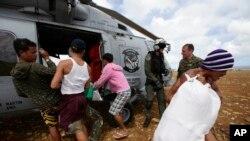 菲律宾风灾地区的居民11月16日在卸下救援物资