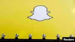 FILE - A billboard displays the logo of Snapchat above Times Square in New York, March 12, 2015.