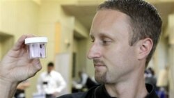 Entomologist Jeff White holds a container of live bed bugs at the North American Bed Bug Summit in Rosemont, Illinois, on September 21