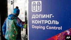 "FILE - A man walks past a sign reading ""Doping Control"" in Russian at a 2014 Sochi Winter Olympics site in Krasnaya Polyana, Russia. Feb. 21, 2014."