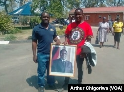 Mourners holding a portrait of the late former president Robert Mugabe in Zvimba communal lands, Mashonaland West.