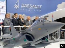 French President Emmanuel Macron, second left, listens to Dassault Aviation CEO Eric Trappier, center, while visiting the Paris Air Show in Le Bourget, June 19, 2017. Macron landed at the Bourget airfield in an Airbus A400-M military transport plane to launch the aviation showcase.