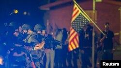 Polisi menodongkan senjata pada sebuah mobil yang melaju ke arahnya di tengah unjuk rasa yang diimbuhi kekerasan di Ferguson, Missouri (18/8).