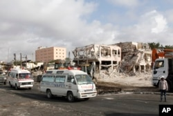 FILE - Ambulances carrying wounded victims pass the scene of Saturday's truck bomb blast, as they head to the airport for victims to be airlifted for treatment in Turkey, in Mogadishu, Somalia, Oct. 16 2017.