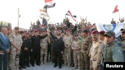하이데르 알아바디 이라크 총리(가운데)가 10일 모술에서 이라크 국기를 들고 ISIL로 부터의 모술 탈환작전 승리를 선언하고 있다.