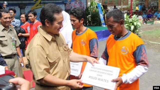 Petugas pemerintah kabupaten Kulonprogo, DI Yogyakarta, memberikan hadiah simbolis yang menyatakan hadiah kambing bagi mereka yang melakukan vasektomi. (VOA/Nurhadi Sucahyo)