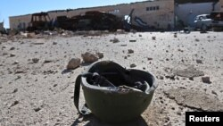 FILE - A helmet belonging to an Islamic State militant is seen on the ground in the town of al-Melabiyyah, south of Hasaka city, Syria, Nov. 24, 2015.