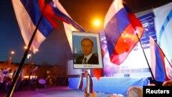 Krımın Simferopol şəhərində keçirilən bayram tədbirində qadın əlində Rusiya prezidenti Vladimir Putinin portretini tutub. 21 mart, 2014.