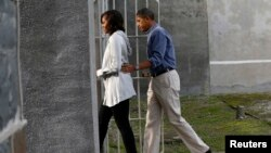 U.S. President Barack Obama and first lady Michelle Obama tour the jail where Nelson Mandela was imprisoned on Robben Island, near Cape Town, June 30, 2013.