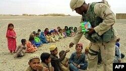 Американский солдат в деревне под Кандагаром угощает конфетами афганских детей.