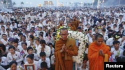 Thousands of mourners pray at the gates of the Royal Palace after the coffin of former king Norodom Sihanouk entered in Phnom Penh October 17, 2012. Tens of thousands poured into Cambodia's capital to witness the procession on Wednesday.