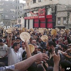 In this citizen journalism image made on a mobile phone and acquired by AP, May 3, 2011, Syrian men carry pieces of bread during a protest against Syrian President Bashar Assad's regime, in the coastal town of Banias