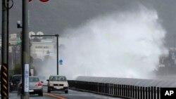 Mobil-mobil berjalan di samping ombak yang tinggi menjelang datangnya topan di Fujisawa, dekat Tokyo, Senin (16/9). (AP/Shizuo Kambayashi)