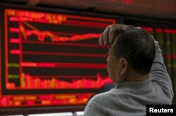A man looks at an electronic board showing stock information at a brokerage house in Beijing, China, Jan. 4, 2016.