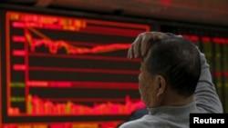 在北京一家证券交易公司,有人观看电子屏幕上的股票信息,屏幕右侧的股价一片惨绿(2016年1月4日)