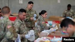 Pasukan Garda Nasional California menyiapkan paket bantuan makanan untuk bantuan makanan para lansia di tengah wabah virus corona, di Indio, California, 26 Maret 2020. (Foto: Reuters)