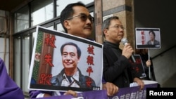 FILE - Pro-democracy Civic Party protesters carry portraits of missing booksellers Lee Bo, left, and Gui Minhai outside the Chinese Liaison Office in Hong Kong, Jan. 19, 2016. Lee Bo returned to his home on March 24, 2016.